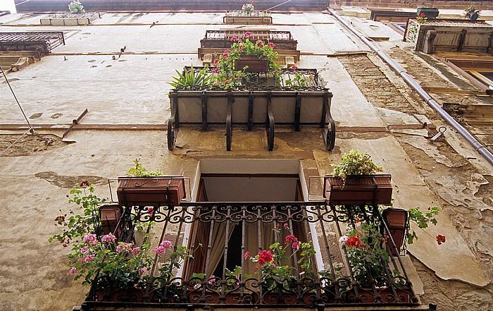 Bosa Corso Vittorio Emanuele II: Schmiedeeiserne Balkone mit Topfpflanzen
